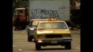 Exterior shots NYC Yellow Taxi Cabs driving along busy street and passengers getting into taxi NYPD Police car drives through traffic with lights and...