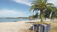 Exterior shots of a beach on Corfu with palm trees and anonymous people sunbathing on May 23 2015 in Corfu Greece