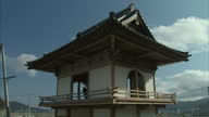 Exterior shots of a Buddhist monk in a pagoda striking a bell in the town of Rikuzentakata one year after it was hit by the devastating Japanese...