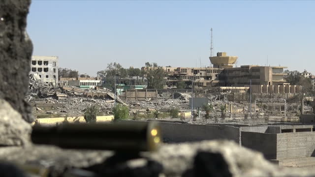 Exterior shots of a bullet shell on a wall overlooking bombed buildings and a YPG sniper taking position on 17 October 2017 in Raqqa Syria