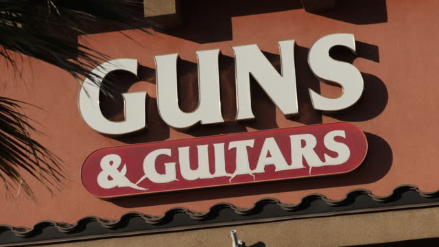 Exterior shots of a closed Guns Guitars store including shots of signs in the window advertising classes for obtaining concealed weapons permits a...