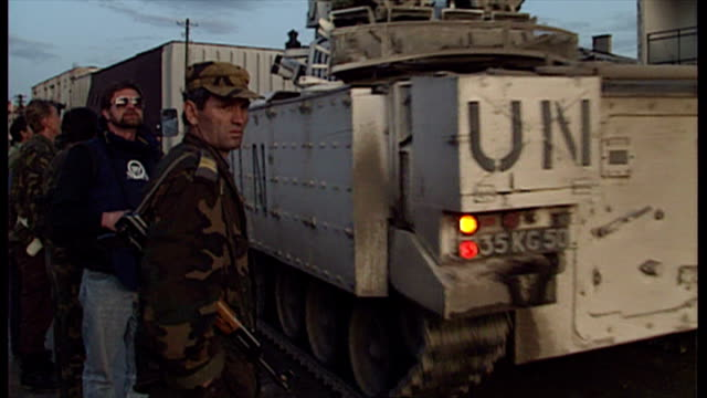 Exterior shots of a convoy of UN Land Rover and a UN APC driving past a group of local people in Srebrenica on April 13 1993 in Srebrenica Bosnia and...