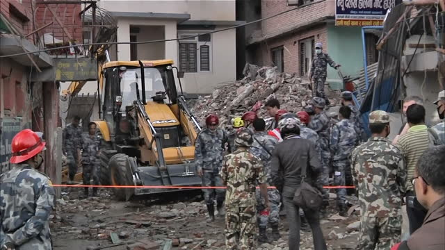 Exterior shots of a digger and rescue teams clearing building rubble from the recent earthquake where buildings were completely destroyed Filmed on...