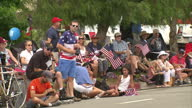 Exterior shots of a fourth of July carnival parade with crowds watching and waving flags on 4 July 2016 in Los Angeles United States