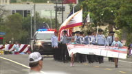 Exterior shots of a fourth of July carnival parade with crowds watching and waving flags and singing 'America the Beautiful' on 4 July 2016 in Los...