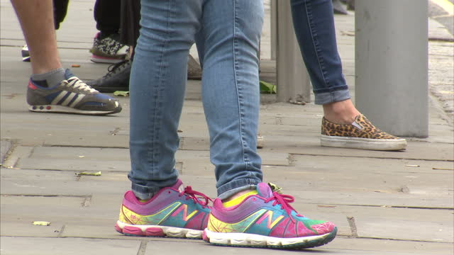 Exterior shots of a group of anonymous people waiting for a bus including women wearing skinny jeans with colourful trainers and plimsolls>> on June...