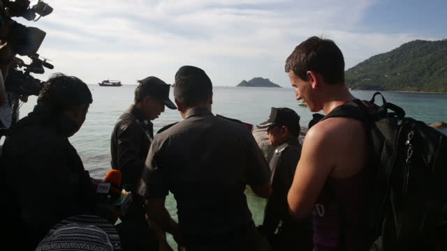 Exterior shots of a group of Thai police and journalists walking across a beach and around rocks on the shore in Koh Tao in the wake of the murders...