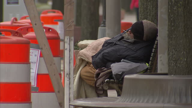 Exterior shots of a homeless man on a park bench smoking on March 5th 2016 in Washington DC