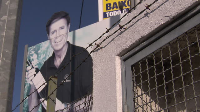 Exterior shots of a large billboard depicting the pop star Cliff Richard advertising Vida Nova wine in Albufeira and traffic passing slowly along...