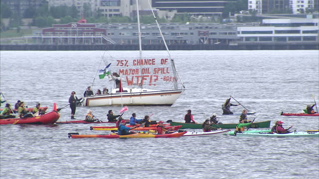 Exterior shots of a large number of environmental activists with signs and forming a flotilla of kayaks in Seattle harbour in protest at plans by...
