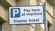 Exterior shots of a parking sensor embedded in a street parking bay parked cars 'pay and display' ticket machine and signage with information about...