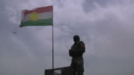 Exterior shots of a Peshmerga fighter sitting in a machine gun turret on an armoured vehicle near the Mosul Dam and another Peshmerga fixing a...