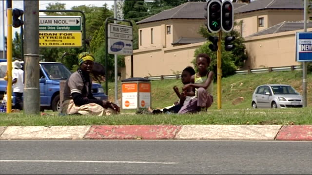 Exterior shots of a poor family sat on a roadside verge eating and a woman begging for change from passing cars on December 05 2007 in Sandton South...