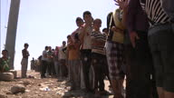 Exterior shots of a queue of displaced people refugees waiting to receive food handouts>> on August 13 2014 in Dohuk Iraq