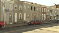 Exterior shots of a rundown area in the Carrollton Ridge neighbourhood of Baltimore with boarded up buildings and refuse piled on the sidewalk...