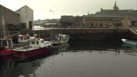 Exterior shots of a Scottish coastal village shows locals milling about square Seagulls on coastal pathway fishing boats moored up in harbor on...