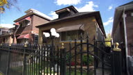 Exterior shots of a sign reading 'Stop Killing People' in window of residential house in Chicago Illinois Families talk about the impact of gun crime...