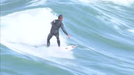 Exterior shots of a surfer catching waves with a surf board off the coast of Newquay on July 28 2015 in Cornwall England