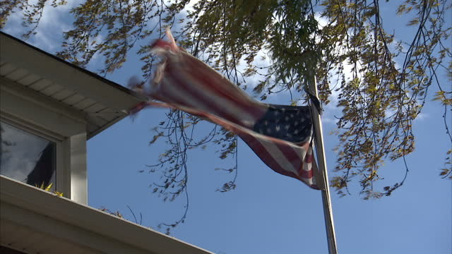 Exterior shots of a tattered Stars Stripes American flag fluttering in breeze on flagpole in garden of house in Chicago Illinois Tattered Stars and...