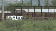 Exterior shots of a US border patrol truck driving slowly along the border fence between Arizona and Mexico on the US side of the border on July 25...