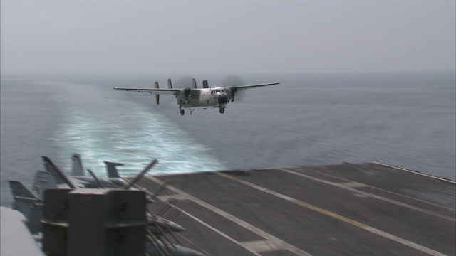 Exterior shots of a US C2A Greyhound landing after mission on the USS Carl Vinson also shows arresting gear resetting on April 04 2015 in At Sea...