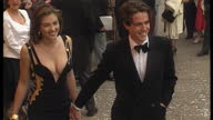 Exterior shots of actress Liz Hurley actor Hugh Grant arriving together at the premiere of Four Weddings a Funeral on May 11 1994 in London England
