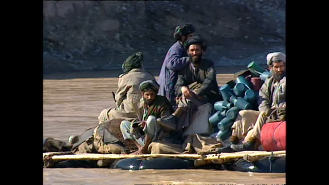 Exterior shots of Afghan people crossing a river in Kala Kata on homemade rafts on October 29 2001 in Kabul Afghanistan