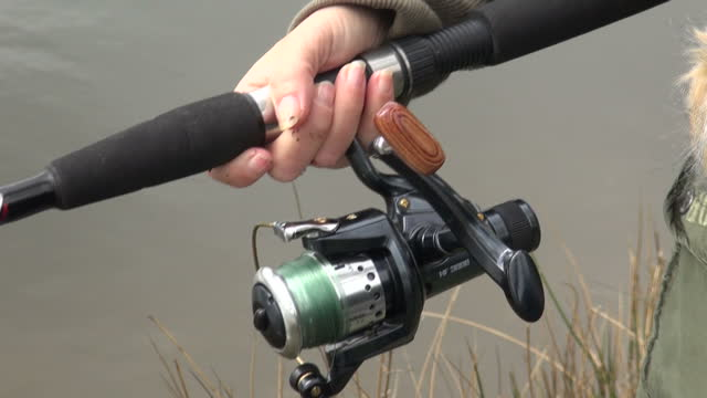 Exterior shots of an anonymous person threading a live worm onto a fishing hook throwing the fishing rod line into a river on 14th April 2012 in...