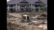 Exterior shots of an area in Khao Lak devastated by the tsunami with shots of a vehicle stacked with coffins and body recovery teams on the scene>>...