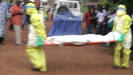 Exterior shots of an Ebola burial team collecting a body from a house being watched by onlookers and prayers being read before the burial team take...