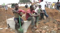 Exterior shots of an Ebola burial team wearing protective clothing burying victims of the Ebola virus on December 18 2014 in Freetown Sierra Leone