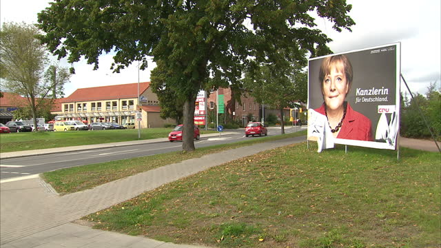Exterior shots of an election poster for Angela Merkel's CDU party which has been partly ripped by vandals Defaced election poster featuring Angela...