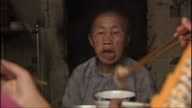 Exterior shots of an extended family eating together in a rural community at home sharing a large bowl of cuisine and using chopsticks on August 17...