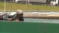 Exterior shots of an illegal migrant crawling across the top of a lorry near Calais and climbing inside the fabric covering and a group of migrants...