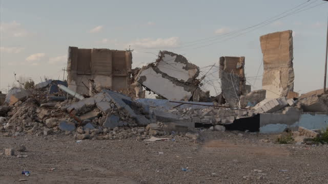 Exterior shots of an Iraqi military controlled road block ISIS militia graffiti on buildings and destroyed buildings from explosions on March 17 2015...