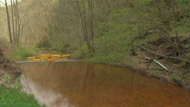 Exterior shots of an orange tinged stream in rural Kentucky polluted with deposits from a nearby coal mine on 7 April 2017 in Hazard Kentucky