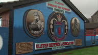 Exterior shots of an Ulster Defence Association loyalist Protestant mural on the end wall of a row of terraced houses featuring a masked paramilitary...