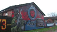 Exterior shots of an Ulster Freedom Fighters loyalist mural on the end wall of a row of terraced houses featuring a masked paramilitary figure...
