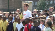 Exterior shots of Andy Murray holding the Wimbledon trophy surrounded by young children and Murray hitting fun shots on court with members of the...