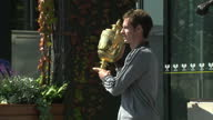 Exterior shots of Andy Murray posing for paparazzi next to a Fred Perry statue holding the Wimbledon trophy Andy Murray with Wimbledon Trophy on July...