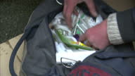Exterior shots of anon person setting up heroin dose fix mixing up substances and heating in a spoon before using needle syringe to take up the...