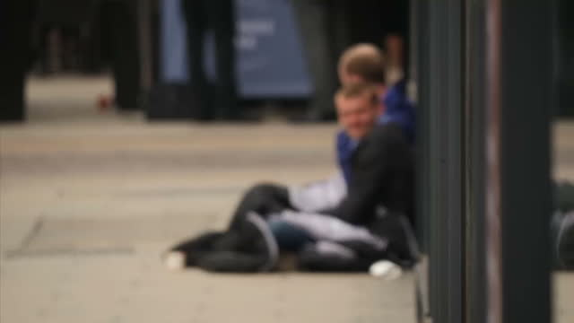 Exterior shots of anonymous homeless sitting on a busy street blurred to hide identity on May 12 2016 in London England