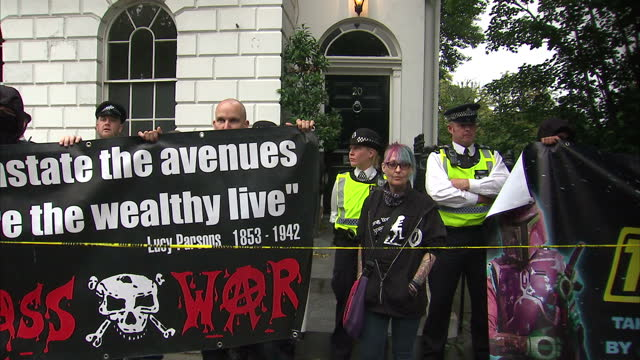 Exterior shots of anti Boris Johnson protesters outside the new Foreign Secretary's home with anticapitalist banners one of them shouting through a...
