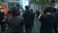 Exterior shots of anti capitalist protesters marching through lower Manhattan past Charging Bull statue near Wall Street chanting 'Whose streets our...