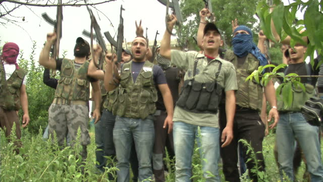 Exterior shots of armed FSA rebels in a group chanting FSA Rebels in Syria on June 24 2012 in UNSPECIFIED Syria