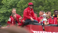 Exterior shots of Arsenal players on an open top bus driving past crowds of cheering Arsenal fans on May 31 2015 in London England