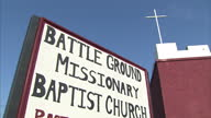 Exterior shots of Battle Ground Baptist Church a red maroon painted church in the Lower Ninth Ward region of New Orleans Also shows grassy areas...