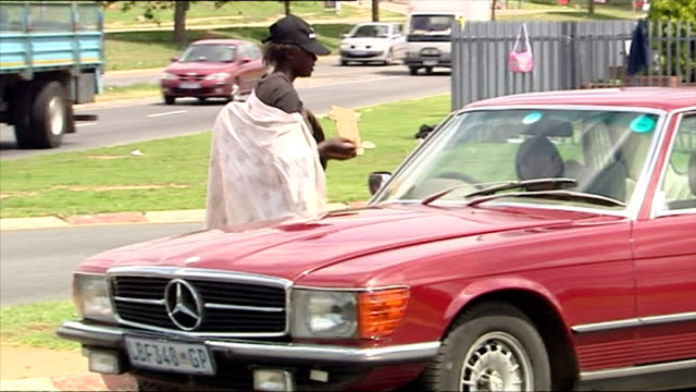 Exterior shots of beggars and street hawkers at the side of a Sandton road plying their trade with drivers stopped in traffic on December 05 2007 in...