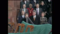 Exterior shots of Bill Clinton and wife Hillary being introduced onto an open air podium during a visit to Londonderry as crowds cheer and wave Stars...