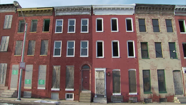 Exterior shots of boarded up windows of abandoned homes on a quiet street on March 15 2017 in Baltimore MD United States
